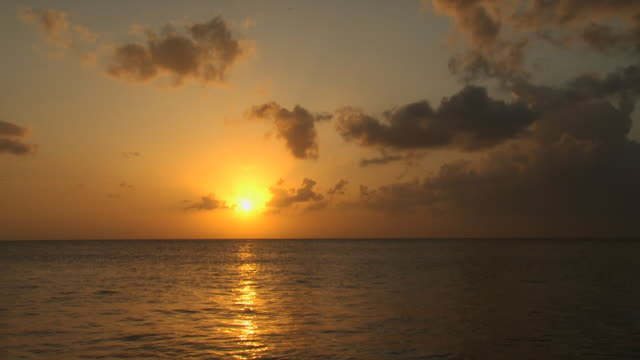 sunrise or sunset over water with clouds - turtle bay hawaii stock videos and b-roll footage