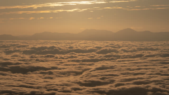 sunrise over a sea of clouds (time lapse/tilt up) - heaven stock videos & royalty-free footage