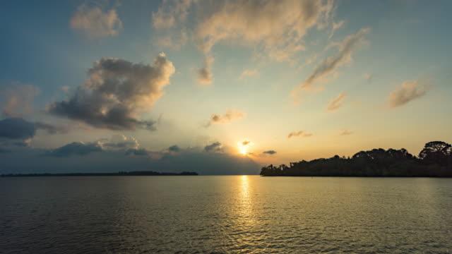 sonnenaufgang über einem ozean mit tropischer insel, zeitraffer-video - meerlandschaft stock-videos und b-roll-filmmaterial