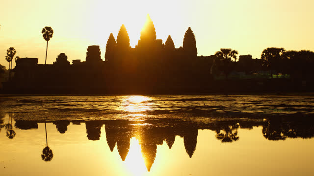 sunrise over angkor wat cambodia in timelapse - temple building stock videos & royalty-free footage