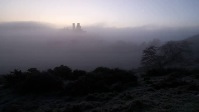sunrise over corfe castle in dorset, where overnight temperatures again dipped below freezing. there has been a castle on the site, which occupies a... - national trust video stock e b–roll