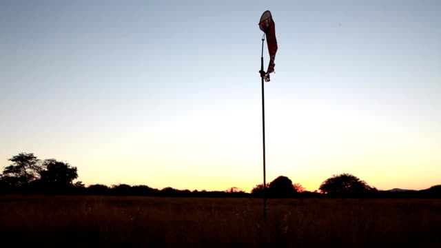 vídeos de stock, filmes e b-roll de t/l ms sunrise over farm runway with windsock/ limpopo/ south africa - biruta