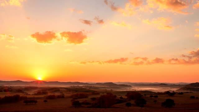 sunrise over hilly landscape of hexigten banner in inner mongolia, china - sunrise dawn stock videos & royalty-free footage