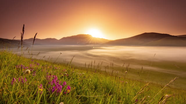 ws time lapse sunrise over idyllic mountains and foggy valley, castelluccio, umbria, italy - landscaped stock videos & royalty-free footage