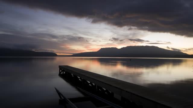 tl ws sunrise over lake and mount tarawera with jetty/ rotorua, new zealand - rotorua stock videos and b-roll footage