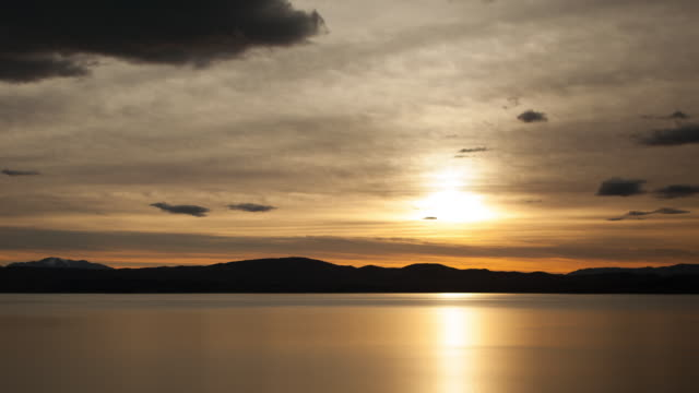 sunrise over lake and mountains - hill stock videos & royalty-free footage