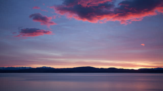 sunrise over lake and mountains - distant stock videos & royalty-free footage