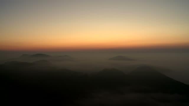 sunrise over landscape covered in fog - ruhige szene stock-videos und b-roll-filmmaterial