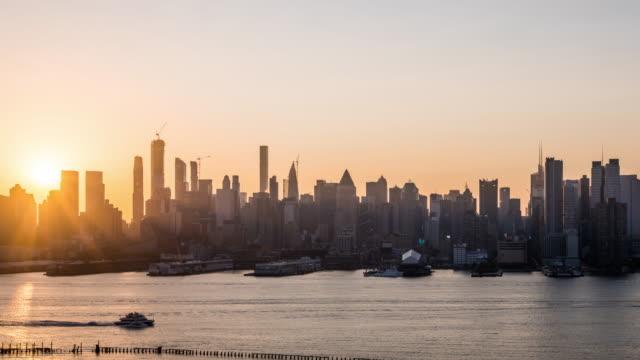 t/l ws pan sunrise over midtown manhattan / new york city, usa - river hudson stock videos & royalty-free footage