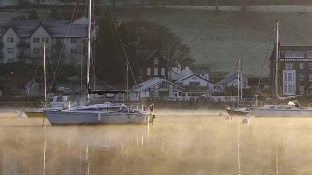 sunrise over mist on lake windermere, at ambleside, lake district, uk. - glowing stock videos & royalty-free footage