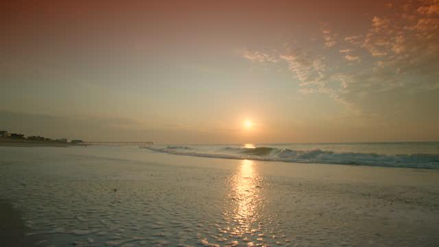 WIDE SHOT sunrise over ocean washing up on beach