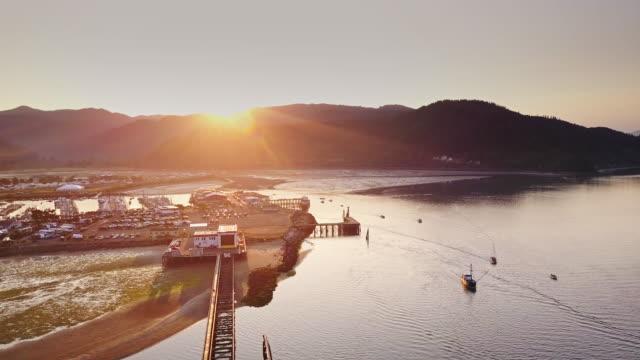 sunrise over oregon fishing village - aerial shot - oregon coast stock videos & royalty-free footage