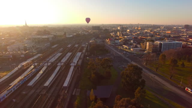Sunrise over Richmond, Melbourne as hot air balloons float across the sky