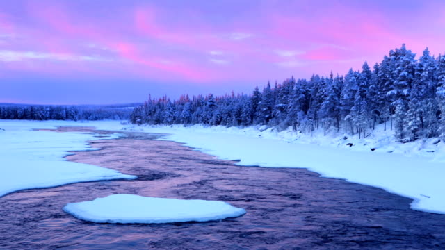 Sunrise over river rapids in a winter landscape, Finnish Lapland