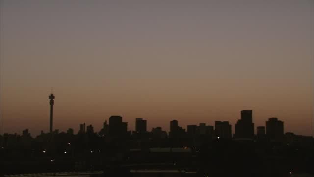 vídeos de stock e filmes b-roll de ws t/l sunrise over skyline of hill brow / johannesburg, gauteng, south africa - joanesburgo