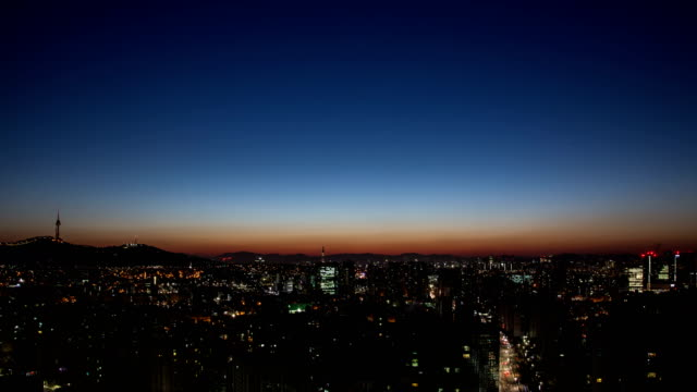 sunrise over the buildings in downtown seoul next to namsan mountain at winter - day stock-videos und b-roll-filmmaterial