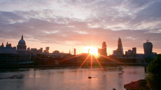 Sunrise over the City of London with boats on the Thames
