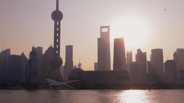 vidéos et rushes de sunrise over the city skyline with the oriental pearl tower, huangpu river, pudong district, shanghai, china, asia - quartier financier