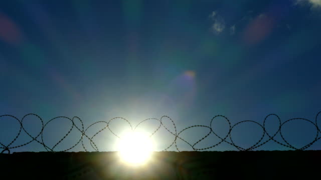 sunrise over the fence with barbed wire (time lapse) - military base stock videos & royalty-free footage