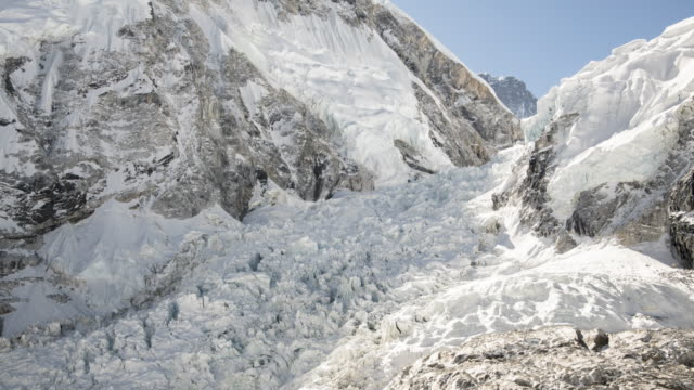 stockvideo's en b-roll-footage met sunrise over the khumbu icefall on mount everest leading up to camp 1 from base camp with a small avalanche - mount everest