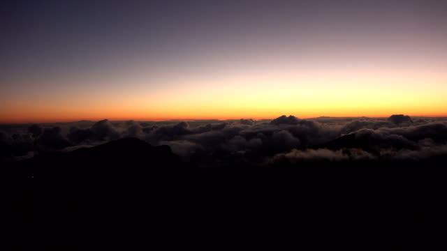 sunrise painting clouds rolling over mountain tops - maroon stock videos and b-roll footage