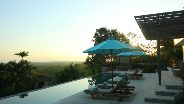 Sunrise panning of luxurious villa property with swimming pool