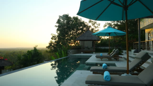 sunrise panning of luxurious villa property with swimming pool - holiday villa stock videos & royalty-free footage