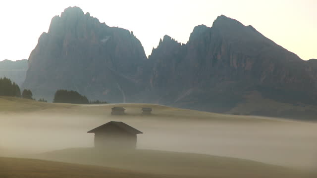 sunrise panorama of the alpine mountains. alpe di siusi, dolomites. italy - コテージ点の映像素材/bロール