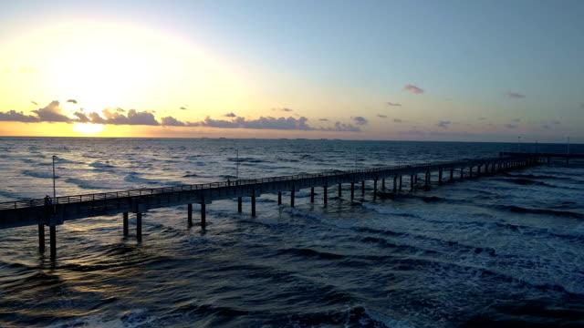 vídeos y material grabado en eventos de stock de muelle de salida del sol a lo largo de estrellarse las olas en playa paraíso - puerto deportivo puerto