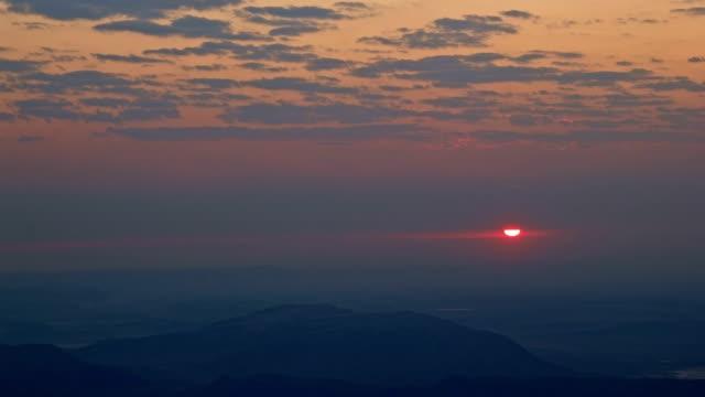 Sunrise red sun peeking through clouds over Alvord Desert from summit of Steens Mountain 1