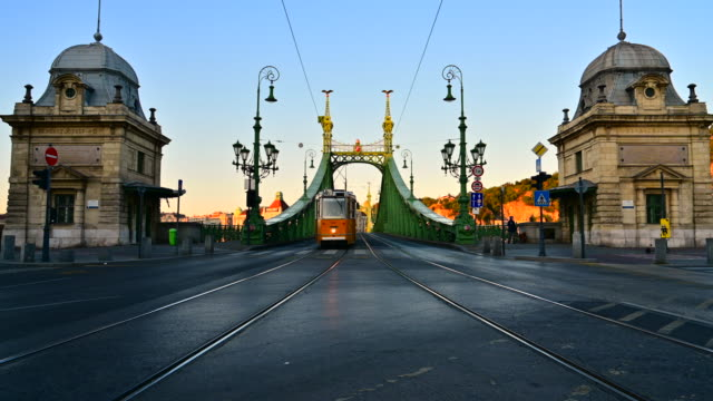 sunrise scene of budapest tram public transport with liberty bridge, budapest, hungary - budapest stock videos & royalty-free footage