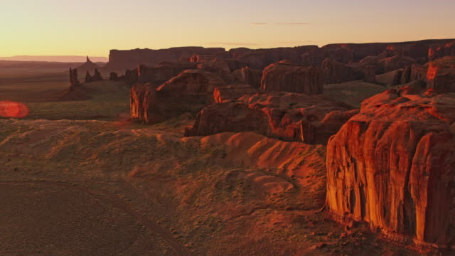 aerial sunrise shining on the steep slopes of mesas and buttes in monument valley, usa - monument valley stock videos & royalty-free footage
