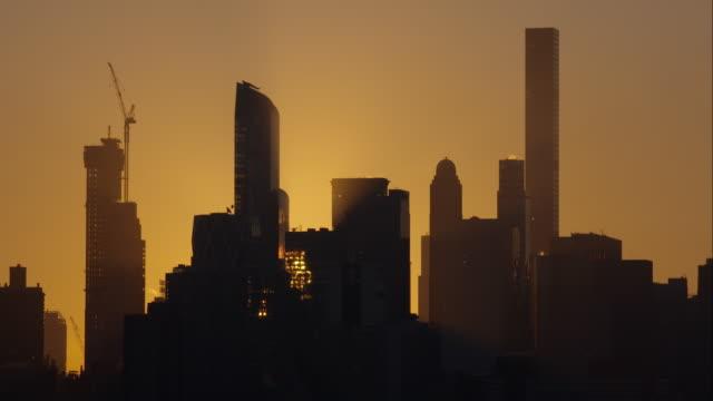 Sunrise shining through New York City skyline against an orange sky