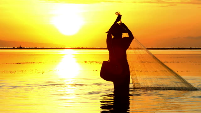 sunrise silhouette balinese man in bamboo hat fishing - indigenous culture stock videos and b-roll footage