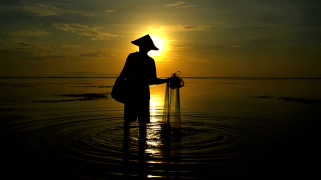 sunrise silhouette balinese man in bamboo hat fishing - 男漁師点の映像素材/bロール