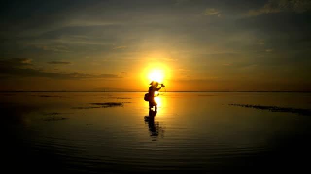 sunrise silhouette balinese man in conical hat fishing - 男漁師点の映像素材/bロール