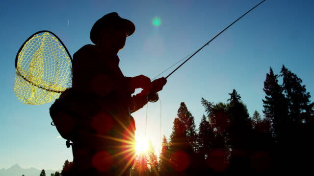 Sunrise silhouette of man fishing for Cutthroat Trout