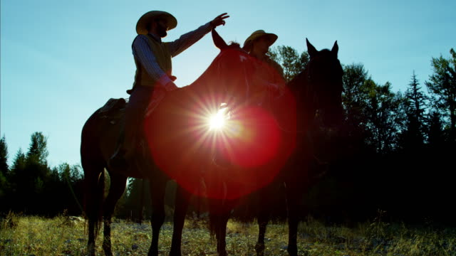 Sunrise silhouette of ranch hands riding horses Canada