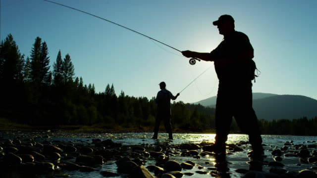 Sunrise silhouette rod and reel fishing in river