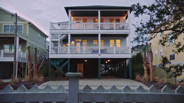 WIDE. Sunrise Sunset exterior of three-story beach house with interior lights on, from behind fence by intracoastal waterway.