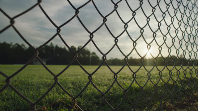 vidéos et rushes de cu sunrise through a chain link fence at a football stadium at dawn - clôture