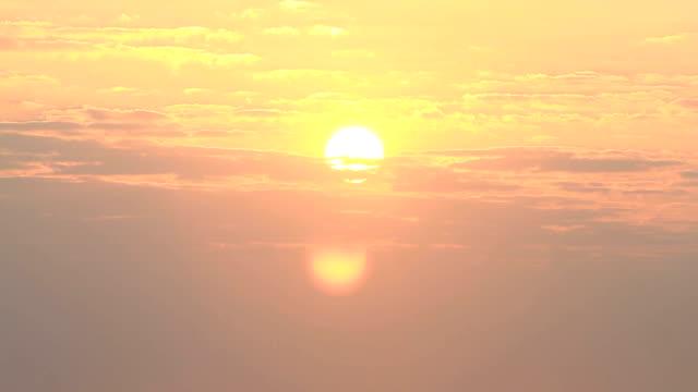 Sunrise through flowing cloud waves, mountain