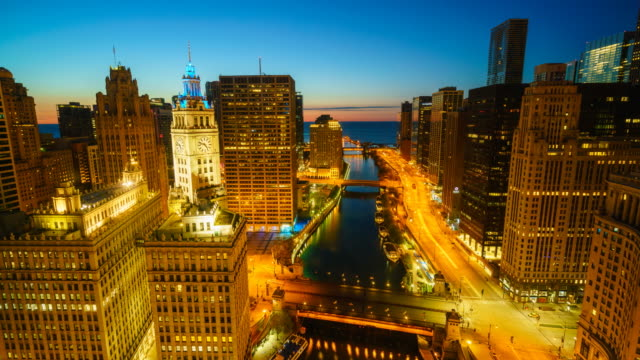 Sunrise time lapse of Chicago cityscape and river towards Lake Michigan, with traffic on bridges and Wacker Drive