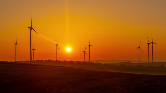 vídeos y material grabado en eventos de stock de t/l salida de lapso de tiempo del amanecer de turbinas eólicas girando en el campo - austria