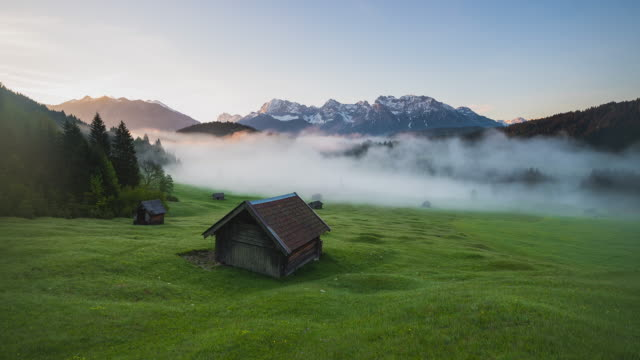t/l sunrise timelapse at lake geroldsee with small huts on a lush green meadow in front and the karwendel mountain range in the back - hut stock videos & royalty-free footage