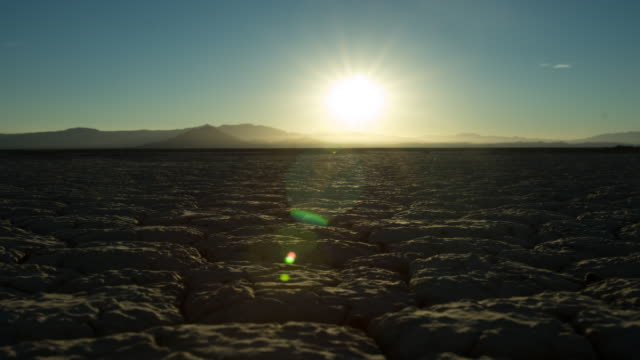 vídeos de stock, filmes e b-roll de sunrise timelapse over dry, caked earth - dry