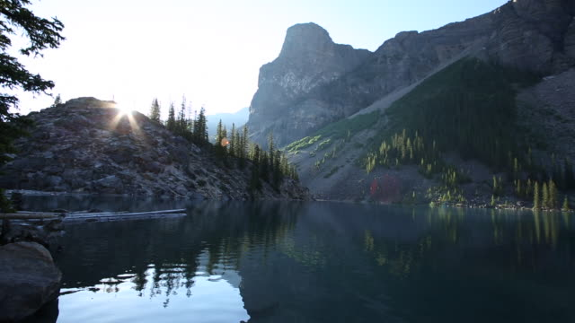 Sunrise view of birds fluttering above mountain lake