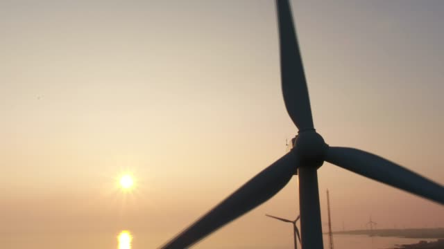 sunrise view of gimnyeong beach and the wind turbine in seogwipo, jeju island, south korea - windkraft stock-videos und b-roll-filmmaterial