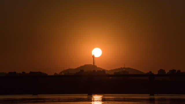 sunrise view of n seoul tower (tourist attraction) behind the han river in seoul - sonnenaufgang stock-videos und b-roll-filmmaterial