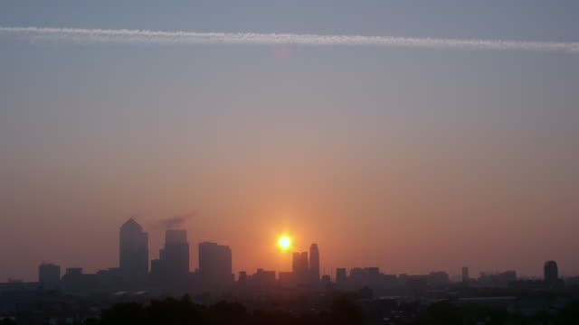 Sunrise with Single Con-trail over Canary Wharf